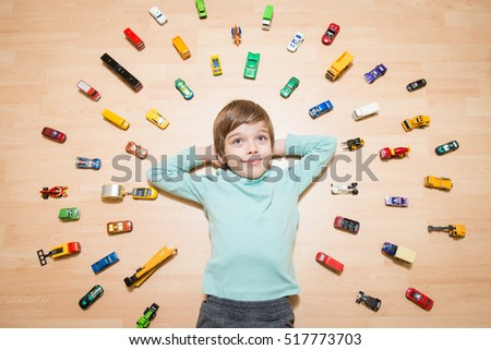 Portrait of happy boy lying on the ground with toy cars around him #517773703