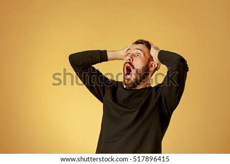 Portrait of young man with shocked facial expression Royalty-Free Stock Photo #517896415