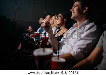 Group of people in theater with popcorn and drinks. Young friends watching movie in cinema. #518102128