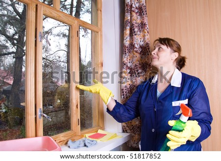 The woman in overalls washes a window #51817852
