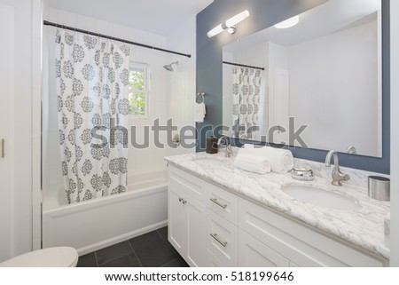 Bathroom with double oval marble sink and shower curtain.  #518199646