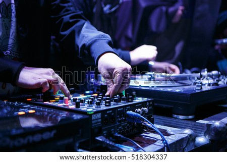 MOSCOW - 15 NOVEMBER,2016: DJ play music show on stage in night club.Disc jockey mix tracks on sound mixing controller,pro audio equipment.Focus on hands #518304337