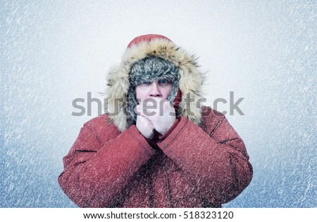 Frozen man in winter clothes warming hands, cold, snow, blizzard Royalty-Free Stock Photo #518323120