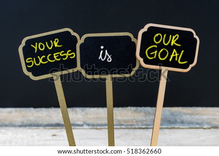 Concept message YOUR SUCCESS IS OUR GOAL written with chalk on wooden mini blackboard labels, defocused chalkboard and wood table in background #518362660