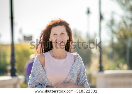 menopausal woman smiling with park in background #518522302