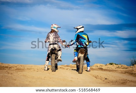 Unrecognizable man and woman in helmets and gear on motorcycles on a background of blue sky and sand