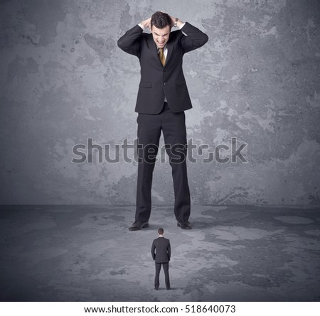 Big angry boss looking at tiny coworker concept on background Royalty-Free Stock Photo #518640073