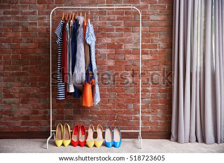 Hangers with different female clothes on brick wall background #518723605