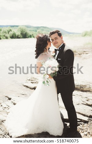 Elegant gentle stylish groom and bride near river with stones. Wedding couple in love #518740075
