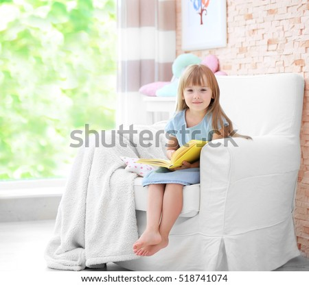 Cute little girl sitting on armchair with book