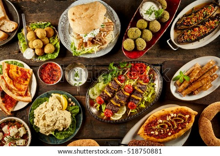 Top down view on freshly prepared delicious varieties of Mediterranean dishes with bread on wooden table #518750881