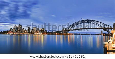 Landmarks of Sydney city CBD across Harbour with bridge, circular quay, passenger terminal and downtown skyscrapers to Kirribilli pier at blue cloudy sunrise. #518763691