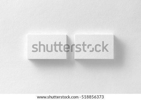 Mockup of two horizontal business cards stacks at white textured paper background.