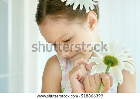 Little girl with dasies flowers #518866399