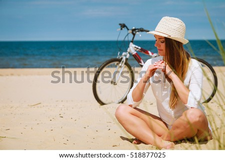 Sport and recreation. Young girl in straw hat resting after cycling on beach. Smiling tourist spending time on seaside. Leisure in summer. #518877025