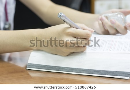 Woman holding a bottle of white pills on the desk in the office room. #518887426