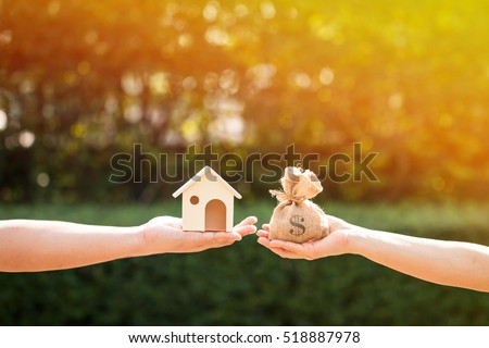 Loans for real estate concept, a man and a women hand holding a money bag and  a model home put together in the public park. Royalty-Free Stock Photo #518887978