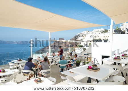Santorini, Greece - October 17, 2015:  Fira, tourists in a bar restaurant on the caldera pathway #518907202