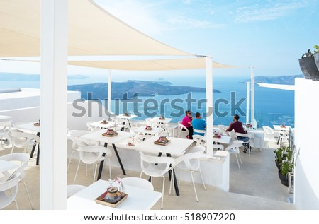 Santorini, Greece - October 17, 2015:  Firostefani, tourists in a bar restaurant on the caldera pathway #518907220