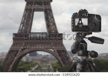 Image of dslr camera on tripod taking picture of Eiffel tower in Paris