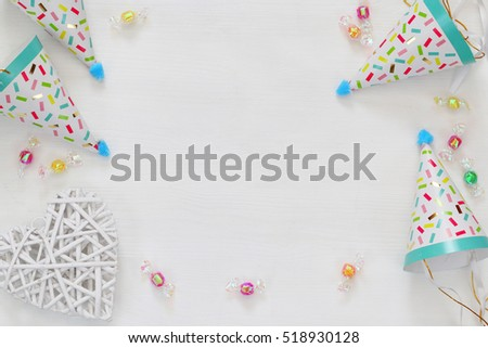 Party hat next to colorful confetti on wooden table. Top view #518930128