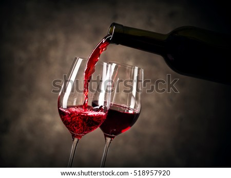 Red wine pouring into glass from bottle shot with selective focus #518957920