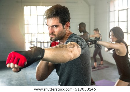 Handsome masculine athlete boxer mma fighter training with fitness group punching aerobox Royalty-Free Stock Photo #519050146