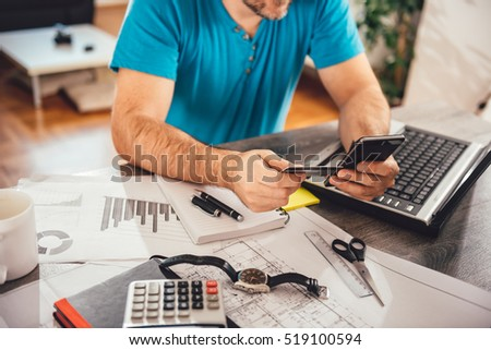Man paying with credit card on smart phone at home office #519100594