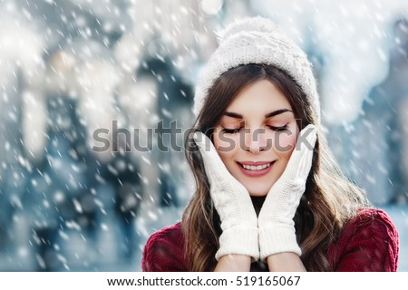 Outdoor close up photo of young beautiful happy smiling girl walking on street. Model closed her eyes and touching face, wearing stylish white knitted winter hat and gloves. Copy, empty space for text