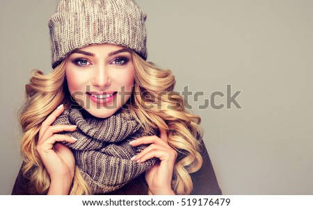 beautiful  young blonde  woman in gray wool winter hat and scarf smiling .  Portrait of beauty  winter girl  in knitted  woolen  clothing hat and  Snood .