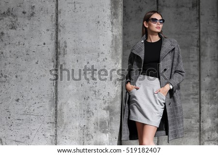 high fashion portrait of young elegant woman outdoor. Grey coat, cat eye sunglasses, grey wall background #519182407