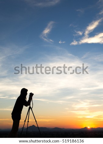 Silhouette of woman shooting with camera at sunset,mountain