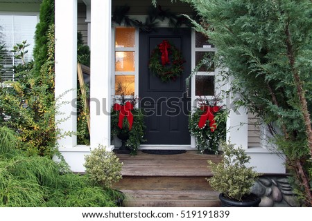 Front door with a Christmas wreath and bows. Also available in vertical. #519191839