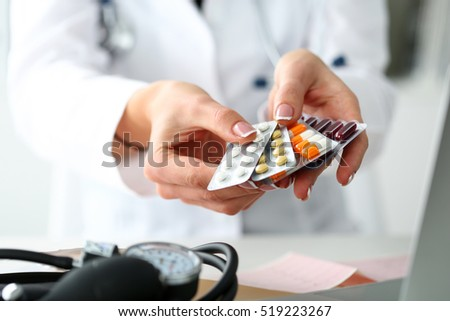 Female doctor hand holding pack of different tablet blisters at workplace closeup. Panacea, life save service, prescribe medicament, legal drug store, disease healing, blood pressure concept #519223267