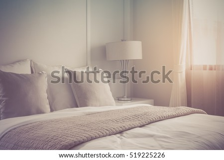 modern lamp on table side with picture frame on wall in bedroom design, vintage process style