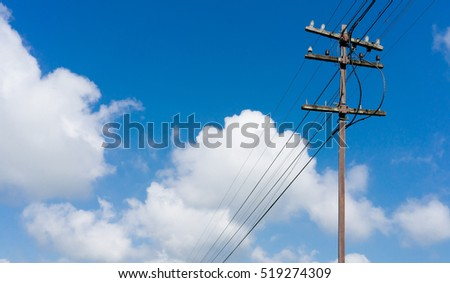 Old wooden electric pole and blue sky background #519274309