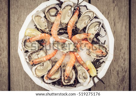 Fresh seafood plate with oysters and shrimps on wooden table., Old fashioned instagram style sepia colors.  #519275176