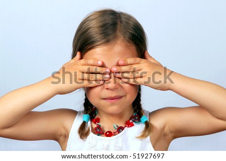 Little girl with her hands covering her eyes #51927697
