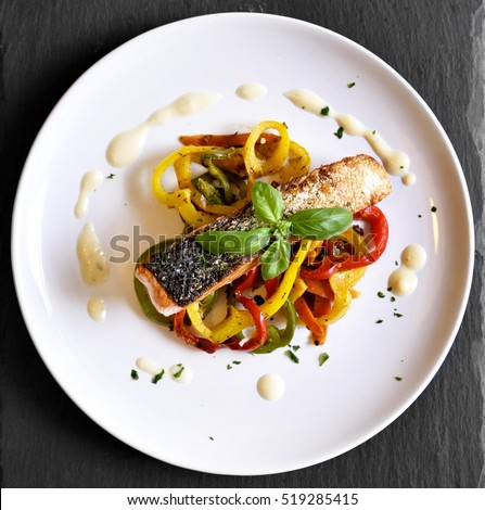 Delicious salmon filet and red bell pepper vegetables on a white plate. High angle shot of a healthy meal, decorated with basil leaf. Royalty-Free Stock Photo #519285415