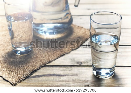 Glasses of water on a wooden table. Selective focus. Shallow DOF. With light effects. #519293908