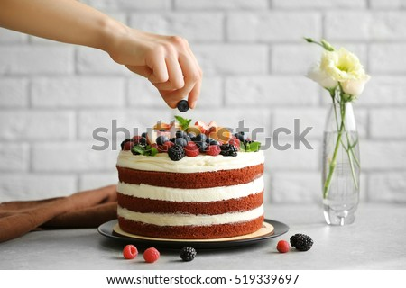 Woman decorating delicious cake #519339697