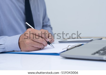 Business man writing on notepad and working on laptop computer in office room, close up. #519343006