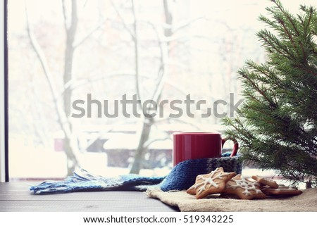 slide figure ginger cookies lying under a green tree on a background of mug and a winter window / warming atmosphere before Christmas #519343225