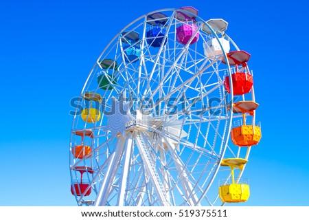 Multicolour ferris wheel on blue sky background #519375511