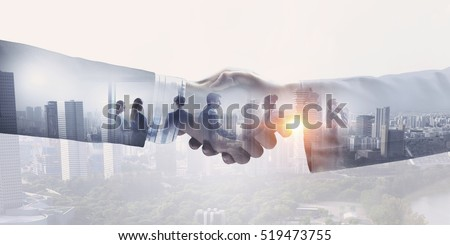 Partners shaking hands . Mixed media Royalty-Free Stock Photo #519473755