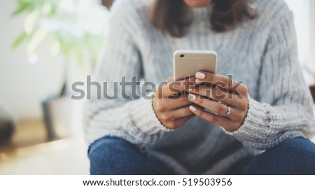 Close-up image of young hipster girl sitting at cozy home interior and using modern smartphone device, female hands typing text message via cellphone, social networking concept Royalty-Free Stock Photo #519503956