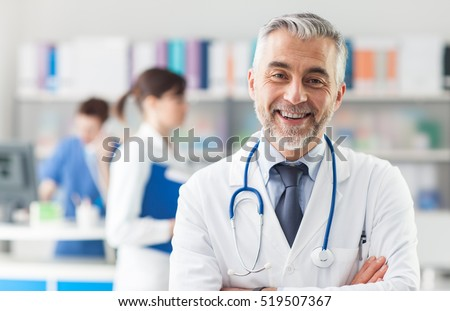 Smiling doctor posing with arms crossed in the office, he is wearing a stethoscope, medical staff on the background Royalty-Free Stock Photo #519507367