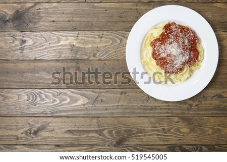 A dinner dish of spaghetti Bolognese on a rustic wooden table top background with blank space at side #519545005