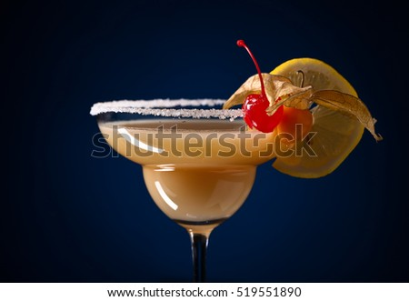 Sweet cocktail with physalis , cherry and lemon  on a dark blue background #519551890