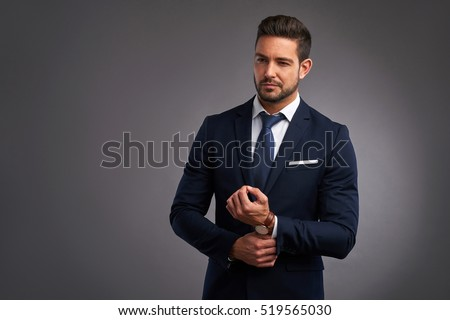 A confident elegant handsome young man standing in front of a grey background in a studio wearing a nice suit Royalty-Free Stock Photo #519565030